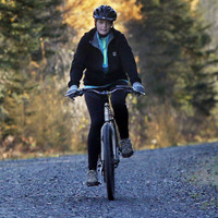 Nurse Kaci Hickox, right, and her boyfriend, Ted Wilbur are followed by a Maine State Trooper as they ride bikes on a trail near their home in Fort Kent, Maine, Thursday, Oct. 30, 2014. State officials are going to court to keep Hickox in quarantine for the remainder of the 21-day incubation period for Ebola that ends on Nov. 10. Police are monitoring her, but can't detain her without a court order signed by a judge.